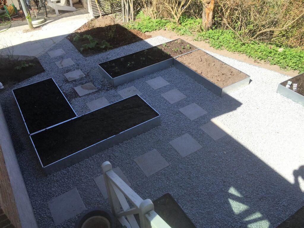 Køkkenhave-anlagt-med-højbede-trædesten-og-granitskærver